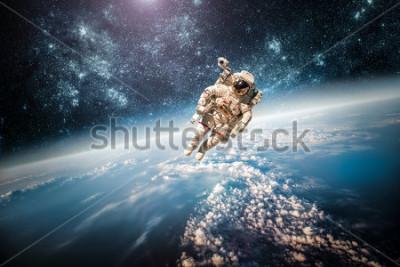 Plakat Astronauta kosmosie na tle planety Ziemia. Elementy tego obrazu dostarczone przez NASA.