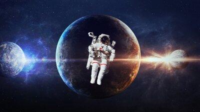 Plakat Astronauta w przestrzeni kosmicznej na tle planety. Elementy tego zdjęcia dostarczone przez NASA