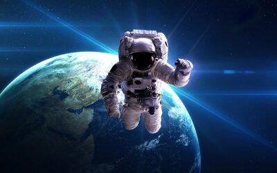 Plakat Astronauta w przestrzeni kosmicznej na tle planety. Elementy tego zdjęcia dostarczone przez NASA.
