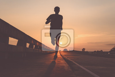 Plakat Athlete runner feet running on road, Jogging at outdoors. Man running for exercise.Sports and healthy lifestyle concept.
