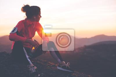 Plakat Athletic kobieta odpoczynku po ciężkim treningu w górach o zachodzie słońca. Sport mocno ubrania.
