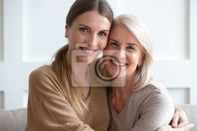 Plakat Attractive aged mother and adult daughter hugging looking at camera