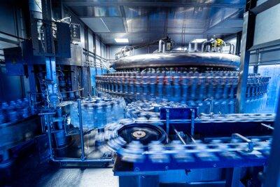 Plakat Automatic filling machine pours water into plastic PET bottles at modern beverage plant.