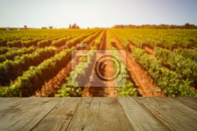 Plakat Autumn vineyard withs unset. Empty space on wooden table for products, deoration or text.