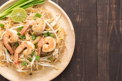 Plakat Azjatycki makaron ryżowy z krewetkami i warzywami na drewnianym stole.