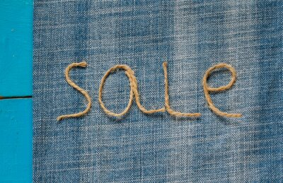 background labeled sale of rope scourges on blue denim background