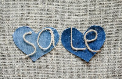 background with sale lettering of rope scourges on blue denim hearts on burlap