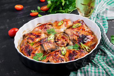 Baked chicken wings in the Asian style on baking dish.