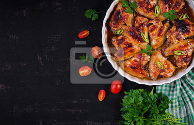 Baked chicken wings in the Asian style on baking dish. Top view, overhead