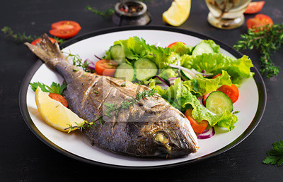 Baked fish dorado with lemon and fresh salad in white plate on dark rustic background. Healthy dinner with fish concept. Dieting and clean eating
