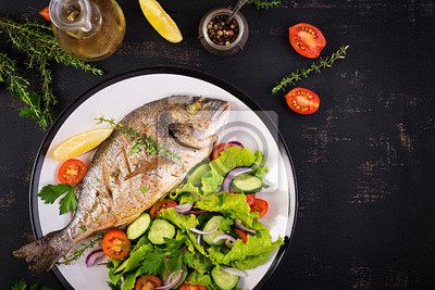 Baked fish dorado with lemon and fresh salad in white plate on dark rustic background. Top view. Healthy dinner with fish concept. Dieting and clean eating