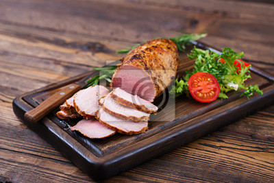 Baked juicy veal fillet in spices on a wooden table. Medium Well.