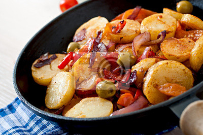Baked potato with vegetables in a frying pan