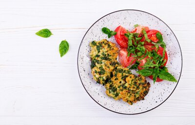 Baked steak chopped chicken fillet with spinach and a side dish of tomatoes salad. European cuisine. Dietary food. Top view