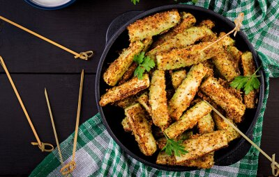 Baked zucchini sticks with cheese and bread crumbs. Vegan food. Vegetarian cuisine. Top view