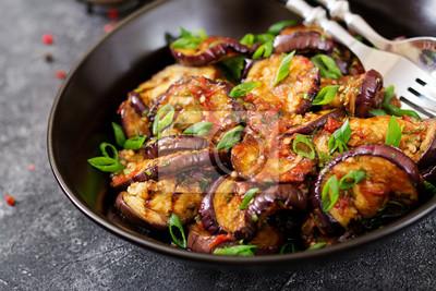 Bakłażan z grilla z sosem pomidorowym, czosnkiem, kolendrą i miętą. Wegańskie jedzenie. Grillowany bakłażan.