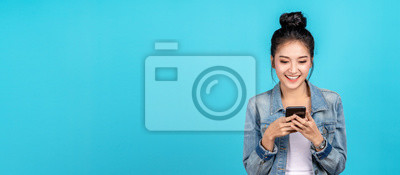Plakat Banner of Happy asian woman feeling happiness and standing typing smartphone on blue background. Cute asia girl smiling wearing casual jeans shirt and connect internet shopping online and surfing.