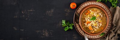 Barley soup with carrots, tomato, celery and meat on a dark background. Banner. Top view.