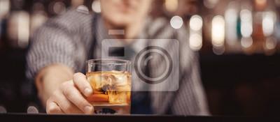 Plakat Barman podaje gościowi szklankę whisky z lodem. Koncepcja odpoczynku w barze