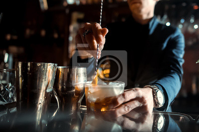 Plakat Barman robi koktajl w barze.