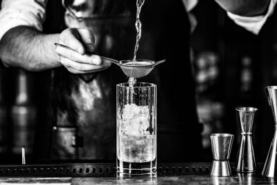 Plakat barmen pouring drink through sieve into glass with ice, black_white photo