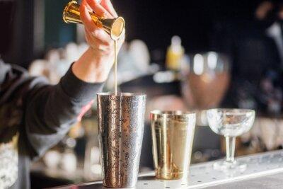 Plakat bartender is preparing a cocktail. Bartender pours a cocktail
