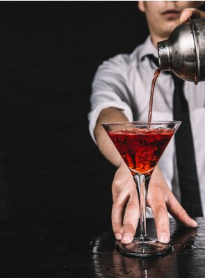 Plakat Bartender making a red martini cocktail. Barman pouring red liquor from a shaker, black background.