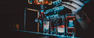 Plakat bartender making collection of colorful shots. Set of cocktails at the bar