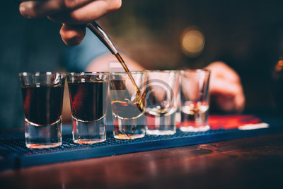Plakat Bartender pouring and serving alcoholic drinks at bar