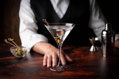 Plakat bartender serving martini in glass at bar