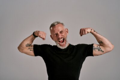 Plakat Be more, do more. Angry middle aged muscular man in black t shirt shouting at camera, showing his biceps while posing in studio over grey background