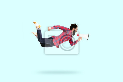 Plakat Bearded hipster man in glasses, jumping and shouting in megaphone, photo over blue background