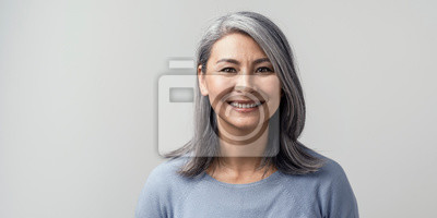 Plakat Beautiful asian with grey hair smiling standing near the wall
