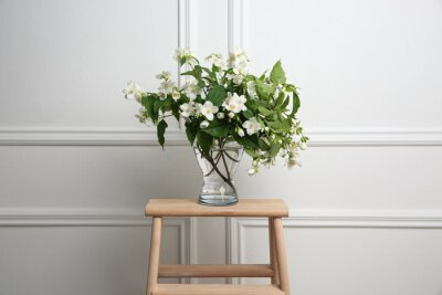 Plakat Beautiful bouquet with fresh jasmine flowers in vase on wooden table indoors