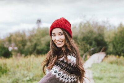 Plakat Beautiful carefree long hair asian girl in the red hat and knitted nordic sweater in autumn nature park