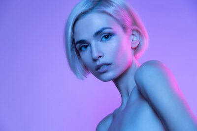 Plakat Beautiful european blond woman trendy glowing neon nude headshot art studio portrait. High fashion stylish image with attractive girl in colorful fashionable light. Perfect female young face