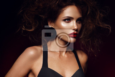 Plakat Beautiful face of a fashion model with red lips. Studio portrait.