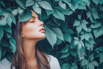 Plakat Beautiful fashion model girl enjoying nature, breathing fresh air in summer garden over Green leaves background. Harmony concept. Healthy beauty woman outdoor portrait