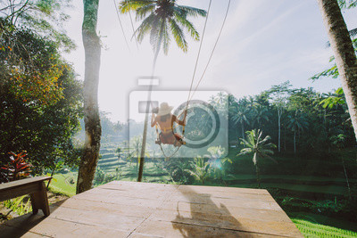 Plakat Beautiful girl visiting the Bali rice fields in tegalalang, ubud. Using a swing over the jungle. Concept about people, wanderlust traveling and tourism lifestyle