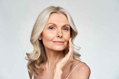 Plakat Beautiful gorgeous 50s mid aged mature woman looking at camera isolated on white. Mature old lady close up portrait. Healthy face skin care beauty, middle age skincare cosmetics, cosmetology concept