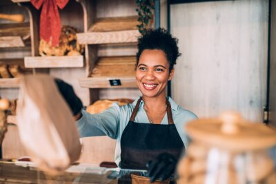 Plakat Beautiful happy African American middle aged female worker working in bakery.