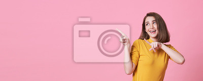 Plakat Beautiful healthy young woman smiling with his finger pointing and looking at on light pink banner background with copy space.