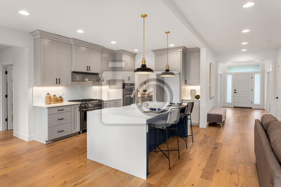 Plakat Beautiful kitchen in new luxury home with waterfall island, quartz counter tops, farmhouse sink, and hardwood floors.
