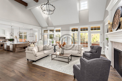 Plakat Beautiful living room and kitchen in new traditional style luxury home. Features vaulted ceilings, and elegant furnishings.. Lights are off.