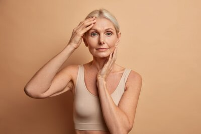 Plakat Beautiful middle aged woman touches face has perfect skin after plastic surgery or collagen injections wears minimal makeup wears cropped top isolated over brown studio background. Aging concept