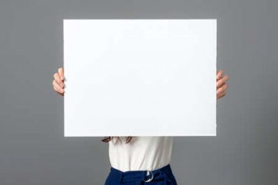 Plakat beautiful sensual business woman with long curly hair shows a blank bilboard, isolated on gray, copy space