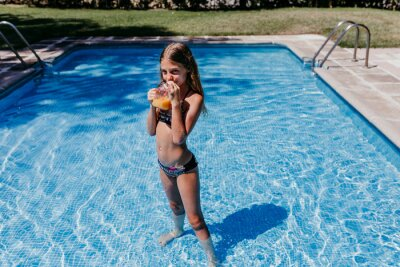 Plakat beautiful teenager girl at the pool drinking healthy orange juice and having fun outdoors. Summertime and lifestyle concept