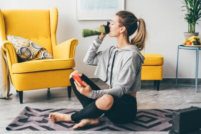 Plakat Beautiful woman drinking smoothie to refresh after workout.