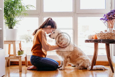 Plakat beautiful woman hugging her adorable golden retriever dog at home. love for animals concept. lifestyle indoors