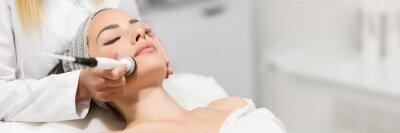 Plakat Beautiful woman in professional beauty salon during photo rejuvenation procedure